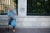 A man wipes his eye next to 'No' campaign graffiti on July 2 2015 in Athens Greece As people continue to queue outside banks Greek finance minister...
