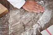 Man wiping flour across work surface
