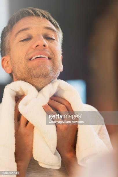 Man wiping neck at bathroom mirror
