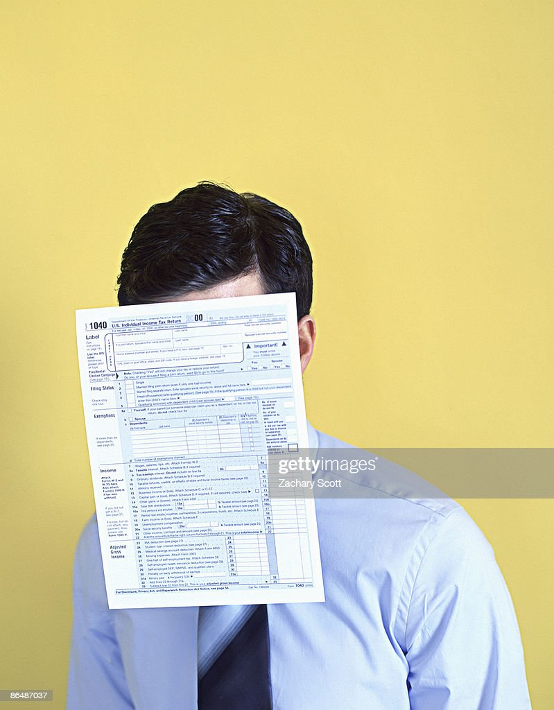 Man With 1040 tax form covering face