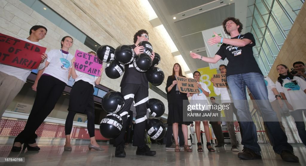 A man with 13 air filled balloons, representing the13 billion surplus Assigned Amount Units (AAUs) of greenhouse gas emission allowances under the Kyoto Protocol, are pinned to his suit during a small protest outside the opening ceremony of the Plenary Session of the United Nations Framework Convention on Climate Change (UNFCCC) in Doha, on December 4, 2012. The first commitment period under the Kyoto Protocol on what will happen to AAUs will expires on December 31.