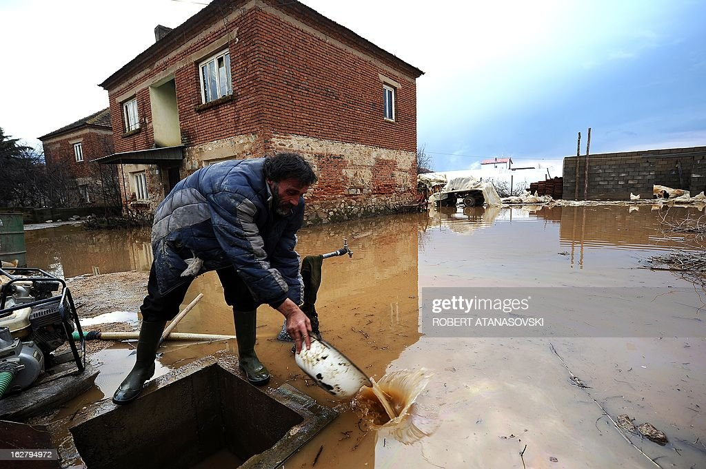 A man with a basin scoops water from the water-meter pit in his flooded yard n the village of Murtino, in the southeastern tip of the Republic of Macedonia on February 27, 2013. The torrential rains which in the last three days poured down on the fertile Strumica Valley inundated fields and villages, destroying or damaging crops and households. Tens of people in the region are now sheltered, as their homes were gravely damaged.