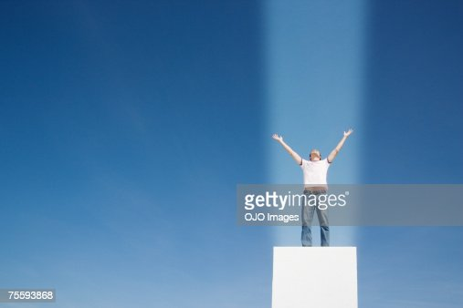 Man with a beam of light shining straight onto him : Stock Photo