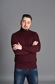 a man with a beard in casual clothes poses on an isolated Gray background, in a burgundy sweater in the studio