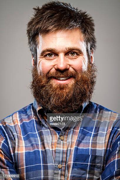 A man with a beard laughing at camera