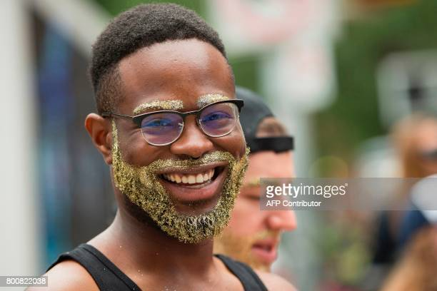 A man with a beard of gold smiles as he watches the Pride Parade in Toronto Ontario June 25 2017 / AFP PHOTO / GEOFF ROBINS