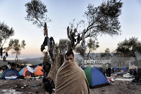 A man with a blanket wrapped around his head and shoulders stands near tents where refugees and migrants live in a field outside the Moria...