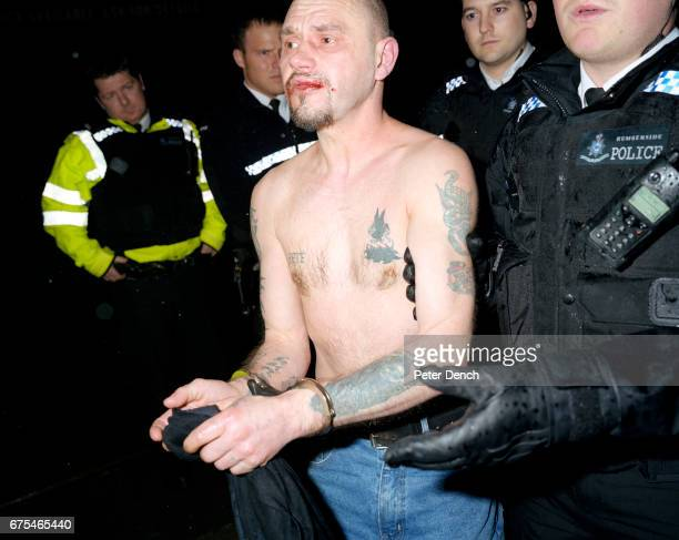 A man with a bloody lip is led away in handcuffs by Humberside Police officers after being arrested for an alleged alcoholrelated public order...