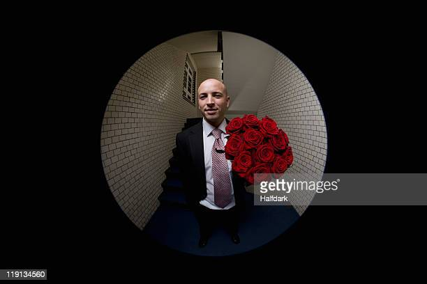 A man with a bouquet of roses viewed through peephole