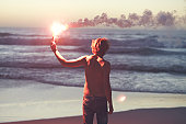 man with a burning flare in his hands by the ocean