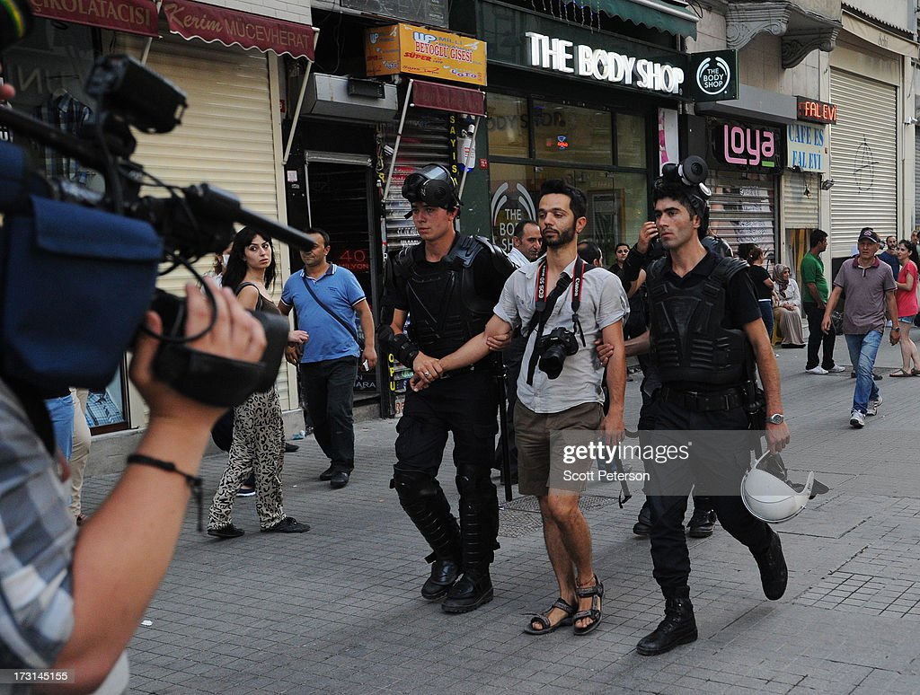 A man with a camera is arrested as Turkish riot police battle anti-government protestors along the Istiklal shopping street near Taksim Square on July 8, 2013 in Istanbul, Turkey. The protests began in late May over the Gezi Park redevelopment project and saving the park trees adjacent to Taksim Square but swiftly turned into a protest aimed at Prime Minister Recep Tayyip Erdogan and what protestors call his increasingly authoritarian rule. The protest spread to dozens of cities in Turkey, in secular anger against Mr. Erdogan and his Islam-rooted Justice and Development Party (AKP).