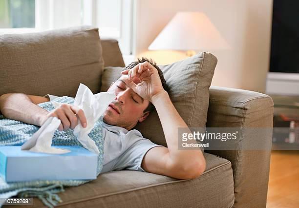 Uomo con un freddo disteso in divano con i tessuti