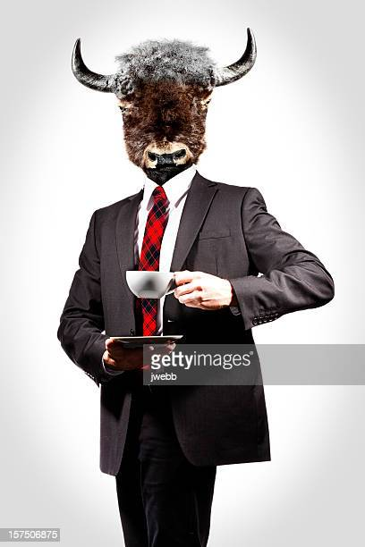 A man with a cow head drinking a hot drink