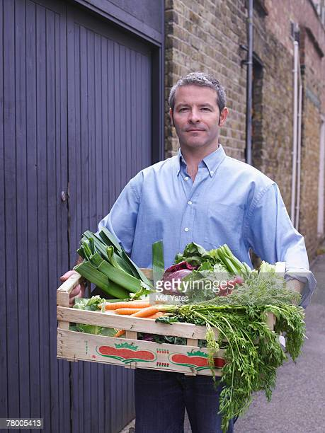Man with a crate of vegetables