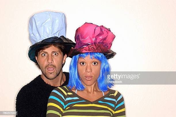 A man with a crumpled black and white hat and a woman with blue hair, a crumpled pink hat look at the viewer with surprised expressions.