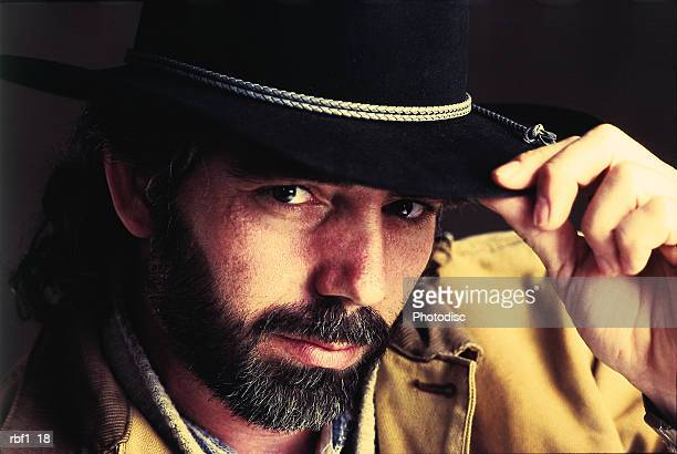 man with a dark mustache and beard and long dark hair wearing a black cowboy hat and yellow jacket tips his hat to the camera