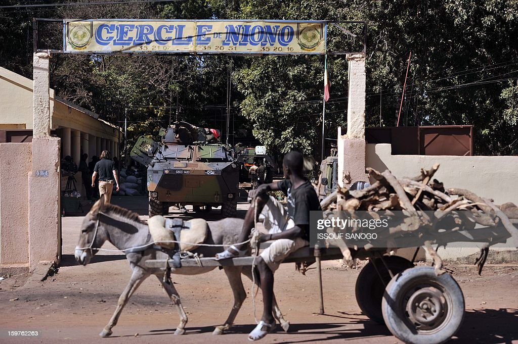 A man with a donkey rides passed French military vehicles on January 20, 2013 in the city of Niono, about 350 kms (220 miles) northeast of the capital Bamako and 60 kms south of Diabaly, which was seized on January 14 by Islamists and then heavily bombed by French warplanes. A spokesman for the French military operation codenamed Serval said on January 20 that French forces were advancing towards Mali's Islamist-held north after taking up positions in the towns of Niono and Sevare.