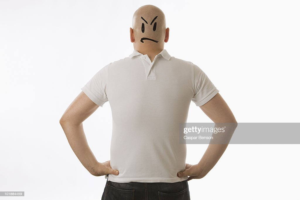 A man with a face drawn on the back of his head and wearing his clothes in reverse