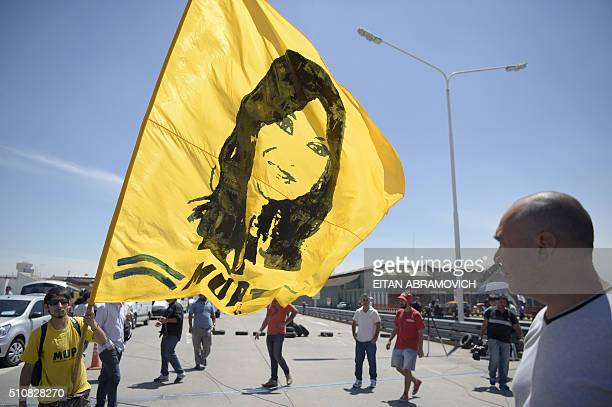 A man with a flag depicting former Argentina's former president Cristina Kirchner joins members of the Tupac Amaru neighborhood association and other...