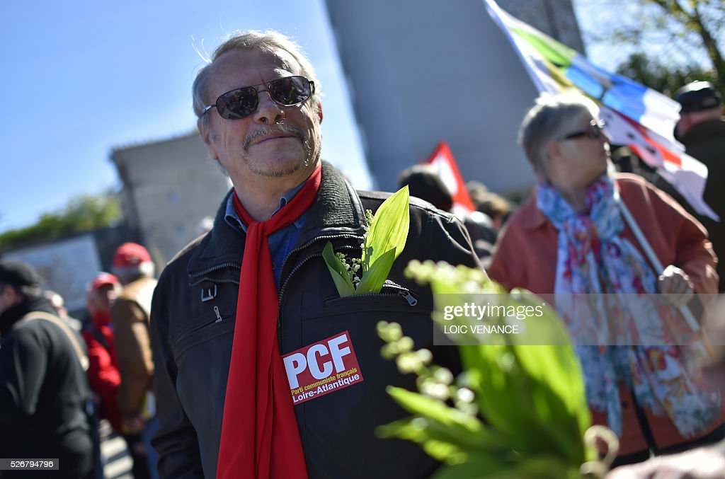 A man with a French Communist Party sticker stands during the traditional May Day rally in Nantes, western France, on May 1, 2016. / AFP / LOIC