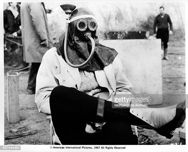 A man with a gas mask sit behind of the movie 'Those Fantastic Flying Fools' circa 1967