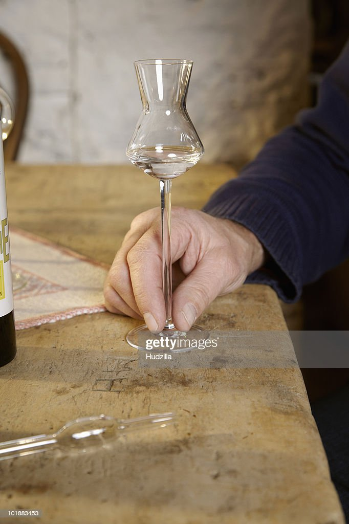 A man with a glass of Schnapps, focus on hand