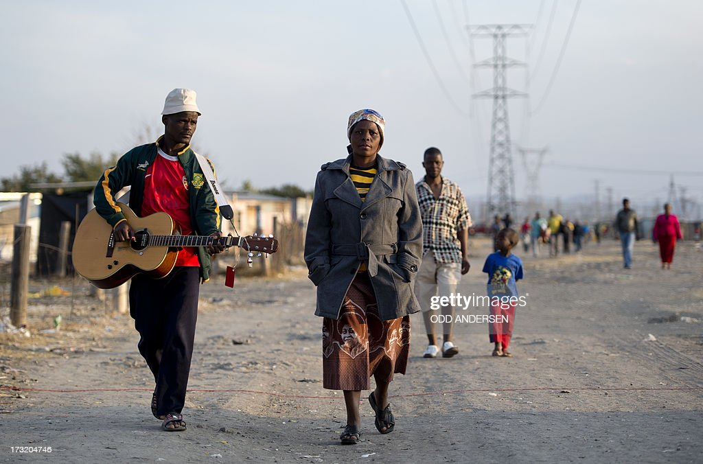 A man with a guitar walks on July 9, 2013 in the Nkaneng shantytown next to the platinum mine, run by British company Lonmin, in Marikana. On August 16, 2012, police at the Marikana mine open fire on striking workers, killing 34 and injuring 78, during a strike was for better wages and living conditions. Miners still live in dire conditions despite a small wage increase. AFP PHOTO / ODD ANDERSEN