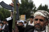 A man with a gun is seen as Houthi supporters stage a protest claiming that the United States obstructs the peaceful settlement in Yemen at Babul...