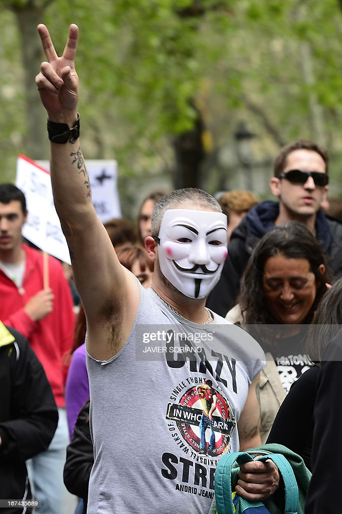 A man with a Guy Fawkes mask flashes the victory sign close to the blocked street leading to the Spain's parliament (Las Cortes) during an anti-government demonstration in Madrid on April 25, 2013. Police in Madrid arrested today four members of anarchist groups suspected of plotting to set fire to a bank and 11 people who blocked access to a university ahead of an anti-government demonstration.