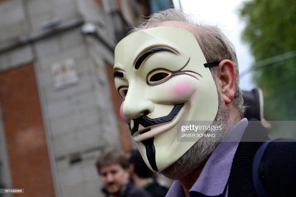 A man with a Guy Fawkes mask stands close to the blocked street leading to the Spain's parliament (Las Cortes) during an anti-government demonstration in Madrid on April 25, 2013. Police in Madrid arrested today four members of anarchist groups suspected of plotting to set fire to a bank and 11 people who blocked access to a university ahead of an anti-government demonstration.