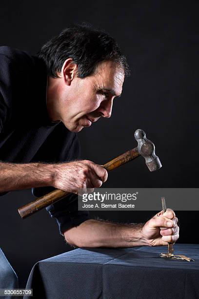Man with a hammer and a punch breaking a clock