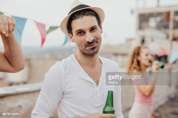 Man with a hat on a rooftop party with his friends