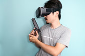 Man with a head mounted display holding a gun.