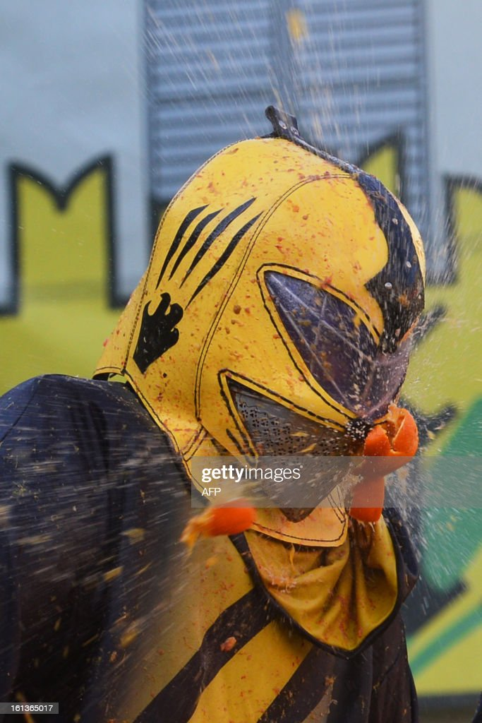 A man with a helmet is hit by an orange during the traditional 'battle of the oranges' held during the carnival in Ivrea, near Turin, on February 10, 2013. During the event which marks the people's rebellion against tyrannical lords who ruled the town in the Middle Ages, revellers parading on floats represent guards of the tyrant, while those on foot the townsfolk.
