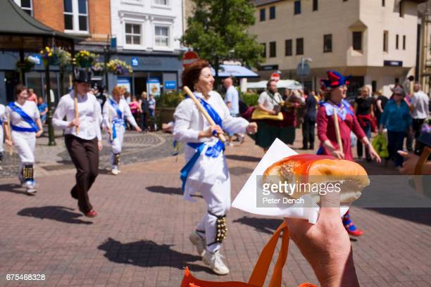 A man with a hot dog watches MorrisWomen perform in Banbury town centre as part of the Hobby Horse festival A hobby horse is a puppetlike costume...