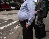 A man with a large waist stands at an intersection May 21 2014 in midtown New York City