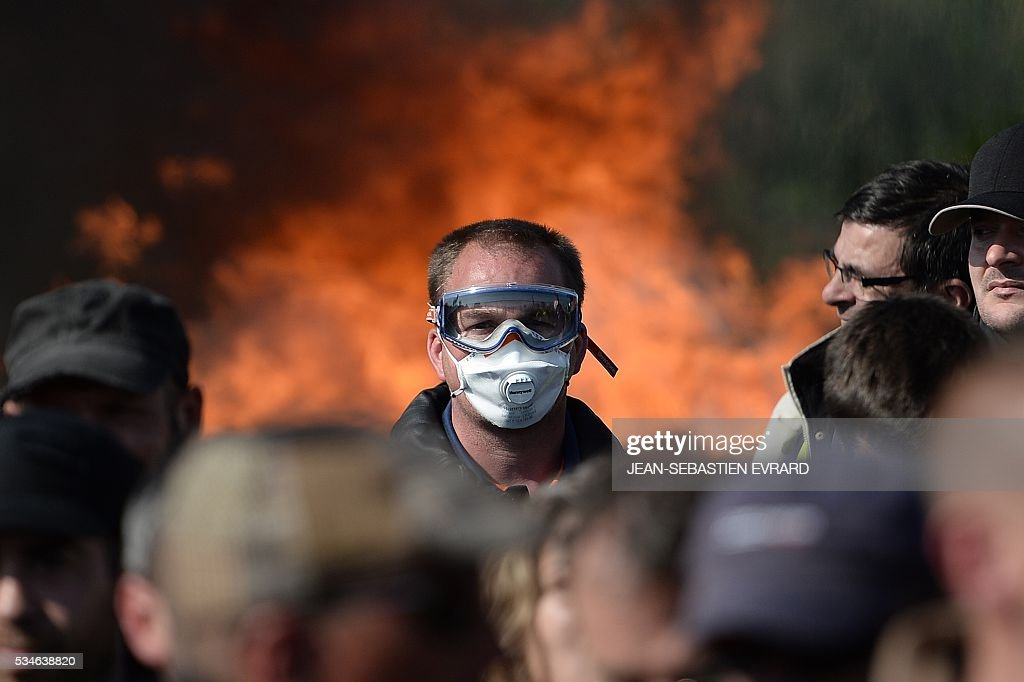A man with a mask is pictured as workers on strike are evacuated by riot policemen as they block the access to an oil depot near the Total refinery of Donges, western France, on May 27, 2016 to protest against the government's planned labour law reforms. The French government's labour market proposals, which are designed to make it easier for companies to hire and fire, have sparked a series of nationwide protests and strikes over the past three months. French unions on May 27 called on workers to 'continue and step up their action', as a wave of strikes against a disputed labour law disrupted transport and fuel supplies. / AFP / JEAN