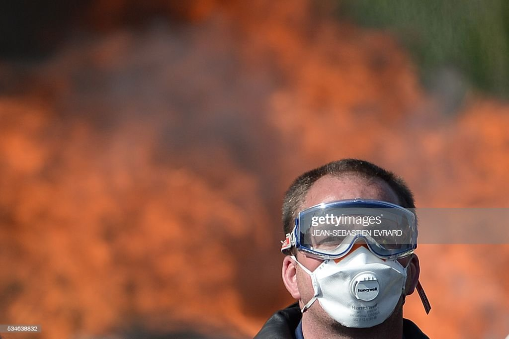 A man with a mask is pictured with fire in background as workers on strike are evacuated by riot policemen as they block the access to an oil depot near the Total refinery of Donges, western France, on May 27, 2016 to protest against the government's planned labour law reforms. The French government's labour market proposals, which are designed to make it easier for companies to hire and fire, have sparked a series of nationwide protests and strikes over the past three months. French unions on May 27 called on workers to 'continue and step up their action', as a wave of strikes against a disputed labour law disrupted transport and fuel supplies. / AFP / JEAN