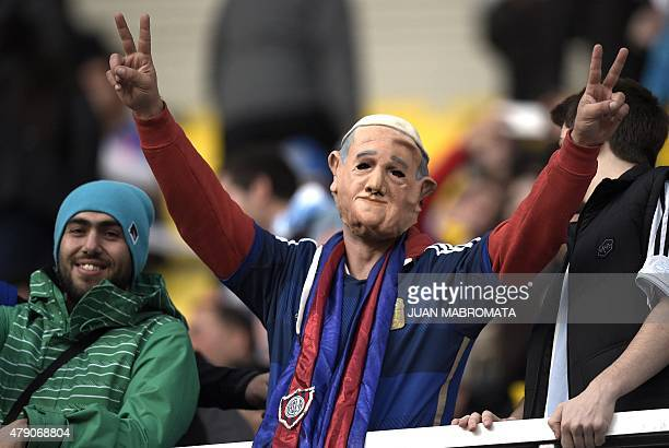 A man with a mask of Pope Francis and a scarf of his team Argentinian San Lorenzo flashes the V sign before the start of the Copa America semifinal...