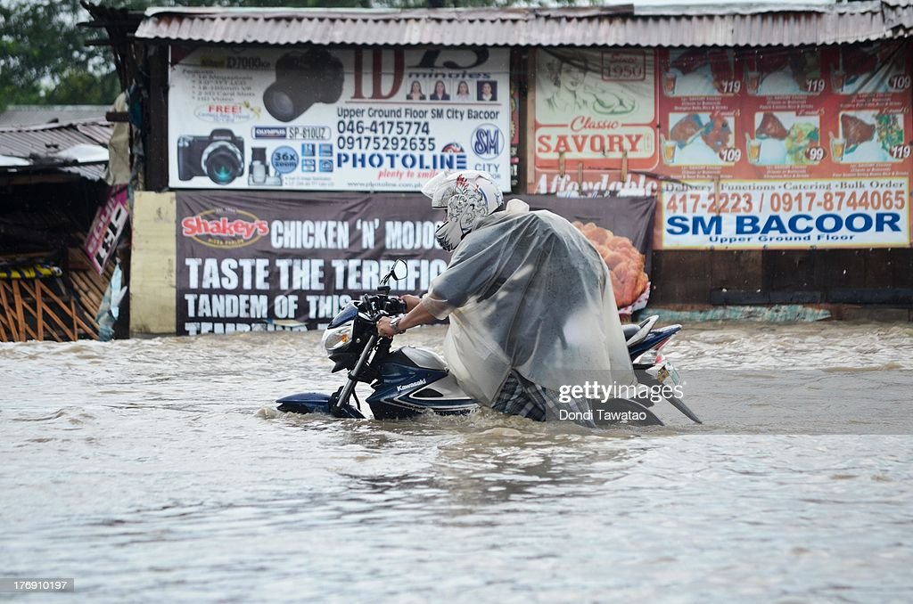 A man with a motorcycle negotiates floodwaters that inundated parts of Las Pinas on August 19, 2013 in Las Pinas City south of Manila, Philippines. Tropical storm Trami which was enhanced by monsoon rains swept overnight through the southern metropolitan cities of Manila and leaving huge parts of four provinces underwater forcing residents to evacuate their homes and seek shelter in evacuation centers. At least three fatalities were recorded with thousands more still needing to be rescued.