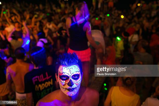 A man with a painted face looks on as hundreds of full moon partiers dance the night away on the beach of Haad Rin on August 22 2013 in Koh Phangan...