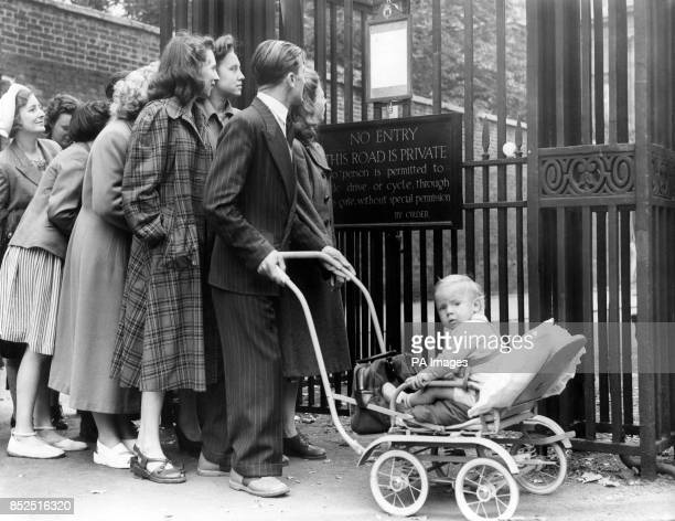Man with a perambulator among the people lines up in a orderly queue to read the official announcement of the birth of a daughter to Princess...