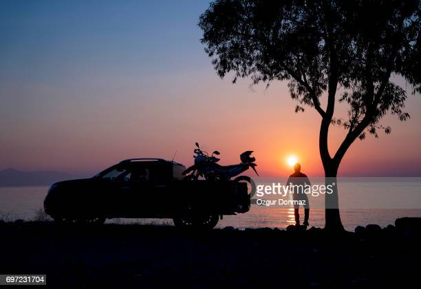 Man with a pickup truck and motorcycle at sunrise