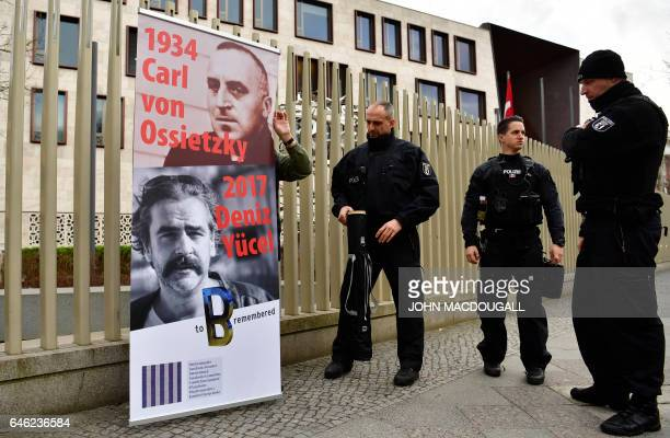 A man with a placard featuring detained German journalist Deniz Yucel in front of Turkish embassy is asked to leave by police in Berlin on February...