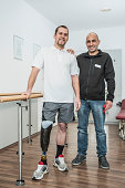 Man with a prosthetic leg and physical therapist