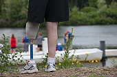 Man with a prosthetic leg standing near a dock and watching the boat race