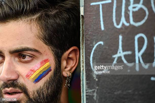 A man with a rainbow flag painted on his cheek looks on as Turkish antiriot police officers fire rubber bullets to disperse demonstrators gathered...