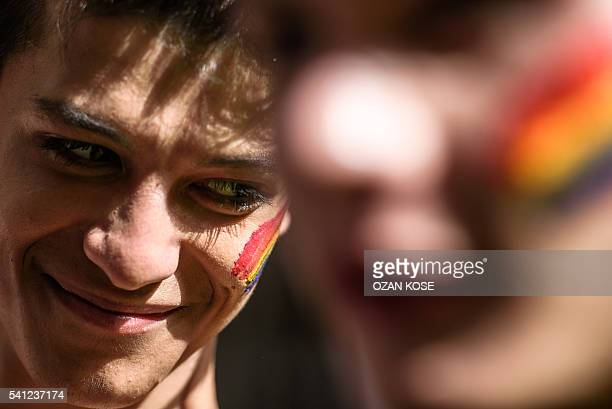 A man with a rainbow flag painted on his cheek smiles as Turkish antiriot police officers fire rubber bullets to disperse demonstrators gathered for...