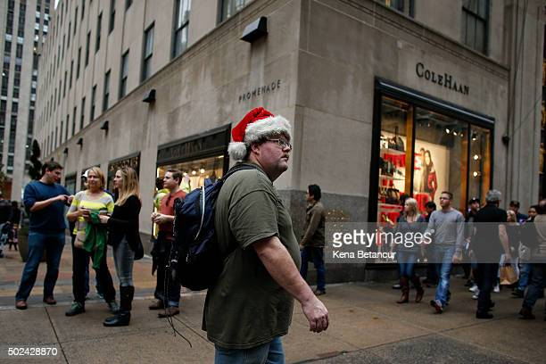 A man with a santa hut wears a tshirt as he walks along 5th avenue near Rockefeller Center on December 24 2015 in New York City New York City has...