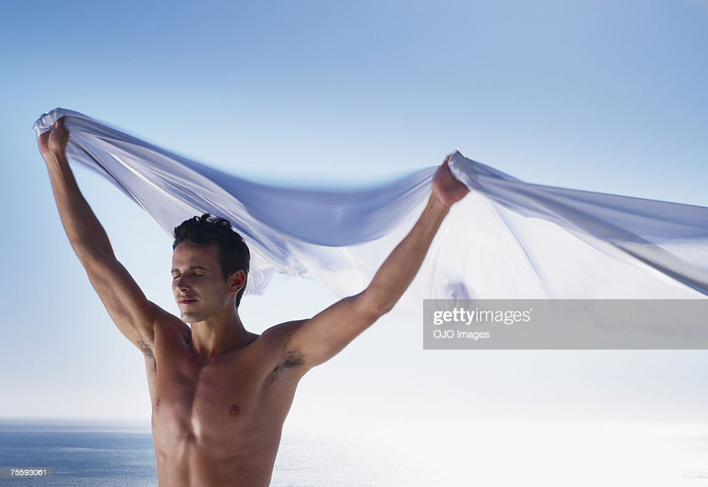 Man with a sheer sheet with ocean backdrop : Stock Photo